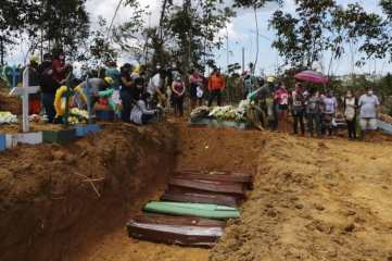 Relatives mourn at the site of a mass burial at the Nossa Senhora Aparecida cemetery, in Manaus, Amazonas state, Brazil, Tuesday, April 21, 2020. The cemetery is carrying out burials in common graves due to the large number of deaths from COVID-19 disease, according to a cemetery official. (AP Photo/Edmar Barros)