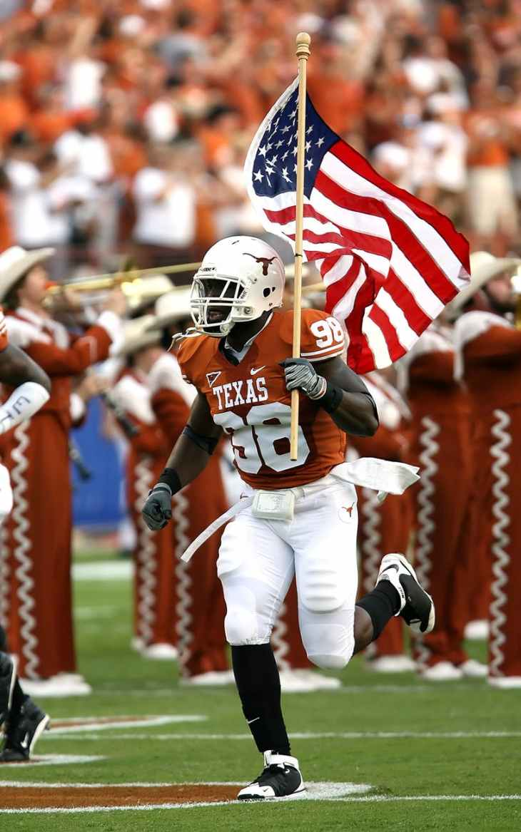 nfl player holding u s a flag on field